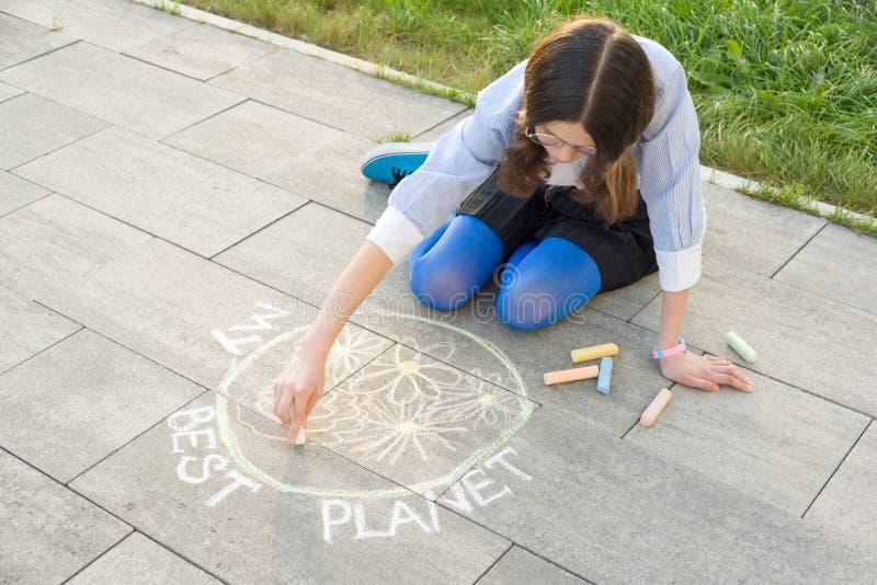 Den tonårs- flickan drar färgpennor på asfaltteckningen - min bästa planet royaltyfri fotografi