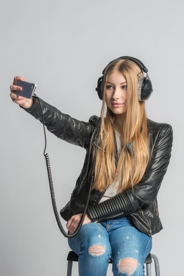 Den tonårs- flickan gör selfie och lyssnande musik från telefonen arkivbild