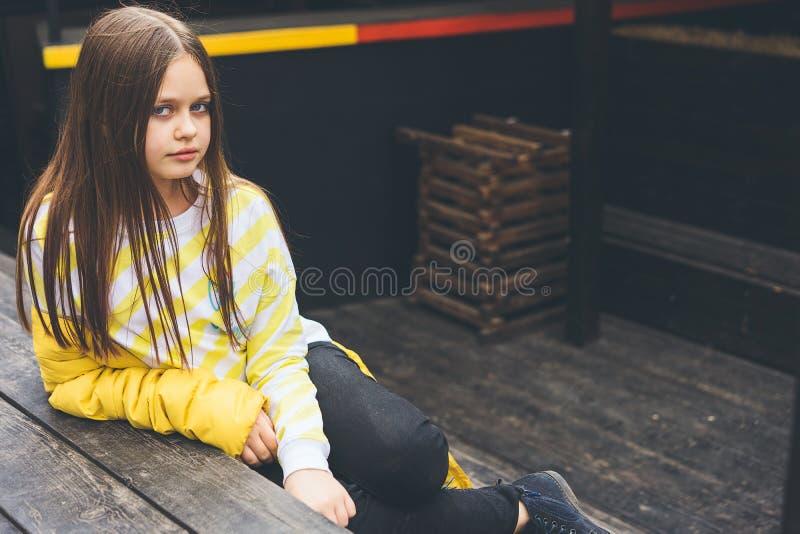 Den tonårs- flickan i gul tröja och svart jeans sitter på en trästruktur royaltyfri foto