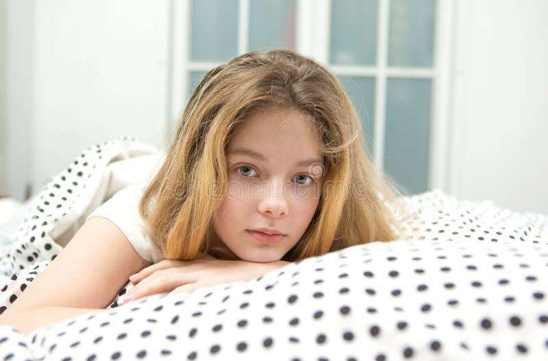 den tonårs- flickan kopplar av i säng arkivfoto