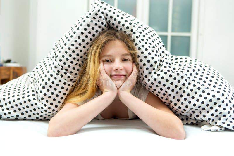 den tonårs- flickan kopplar av i säng royaltyfri fotografi