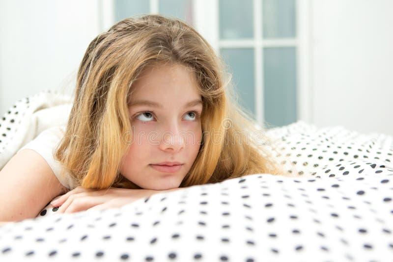 den tonårs- flickan kopplar av i säng royaltyfri bild