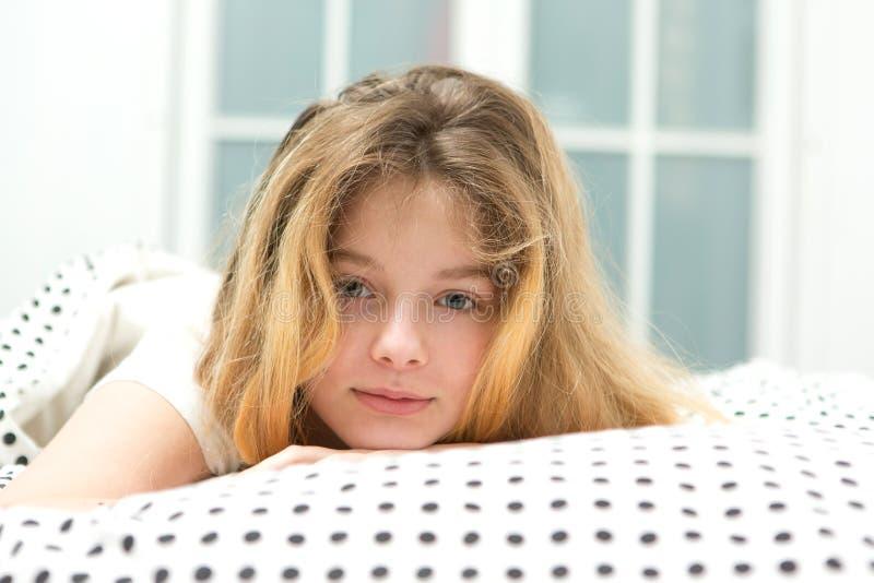 den tonårs- flickan kopplar av i säng arkivbild