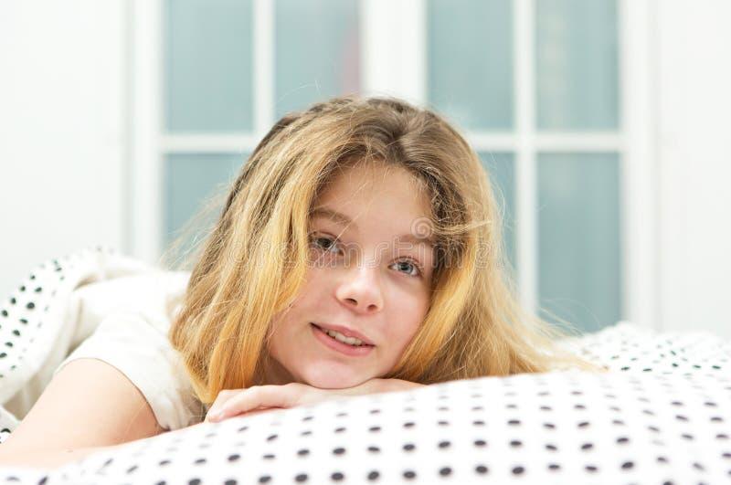 den tonårs- flickan kopplar av i säng arkivbilder