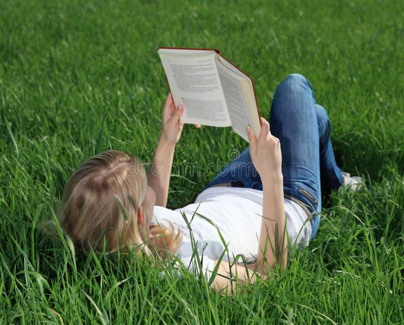 Den tonårs- flickan läser en bok på äng royaltyfri fotografi