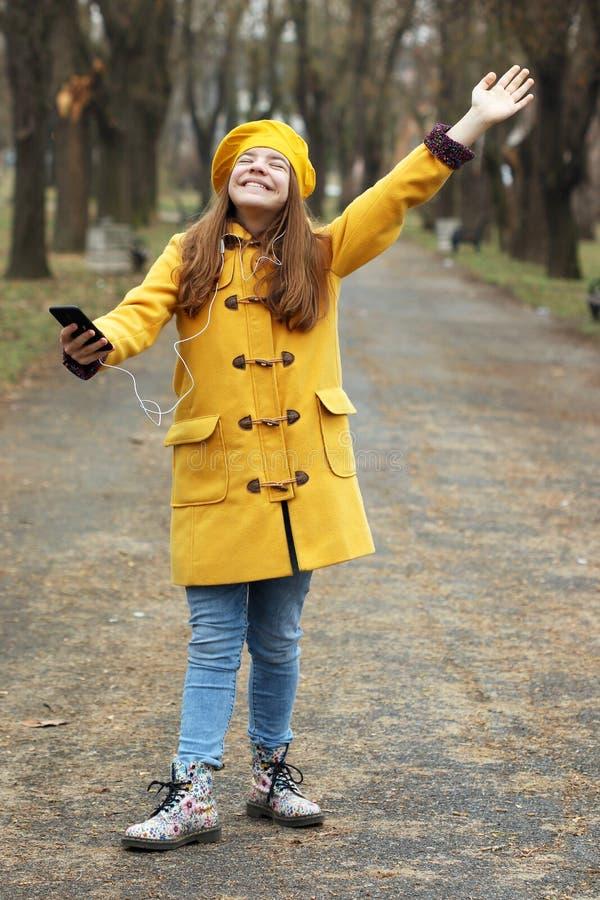 Den tonårs- flickan lyssnar till musik på smartphonen, medan regnet faller arkivbild