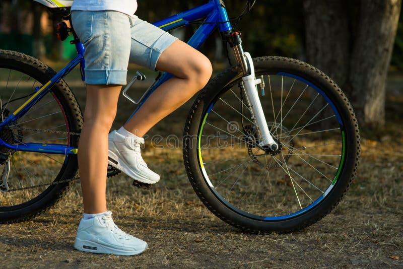 Den tonårs- flickan med cykeln i staden parkerar royaltyfri bild