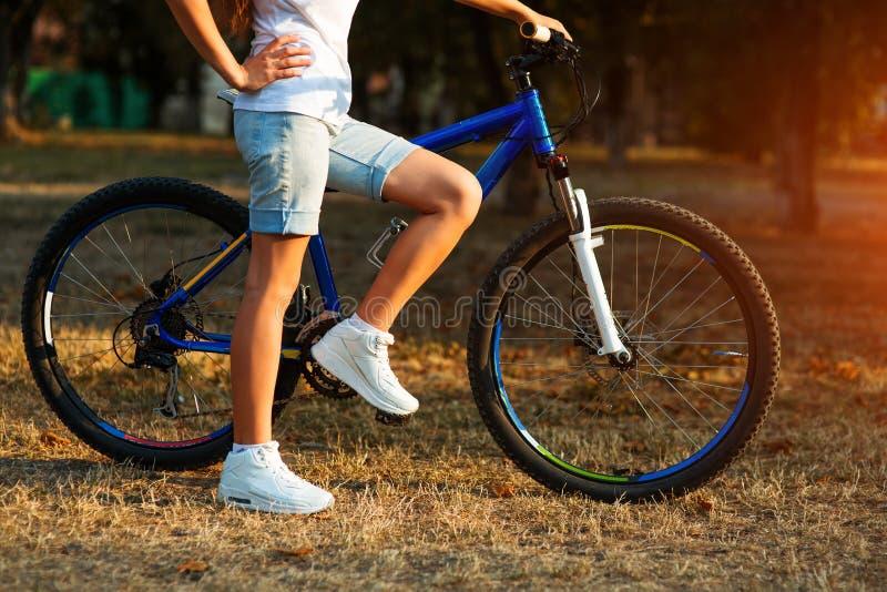 Den tonårs- flickan med cykeln i staden parkerar arkivbilder