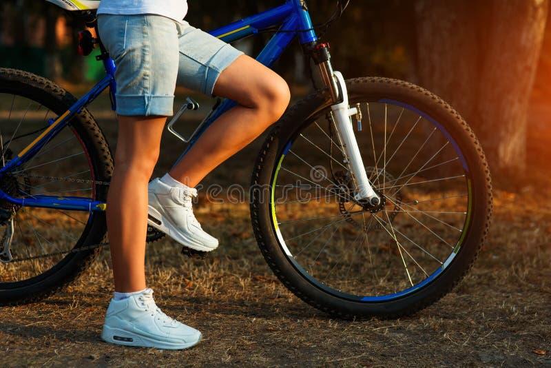 Den tonårs- flickan med cykeln i staden parkerar arkivfoton