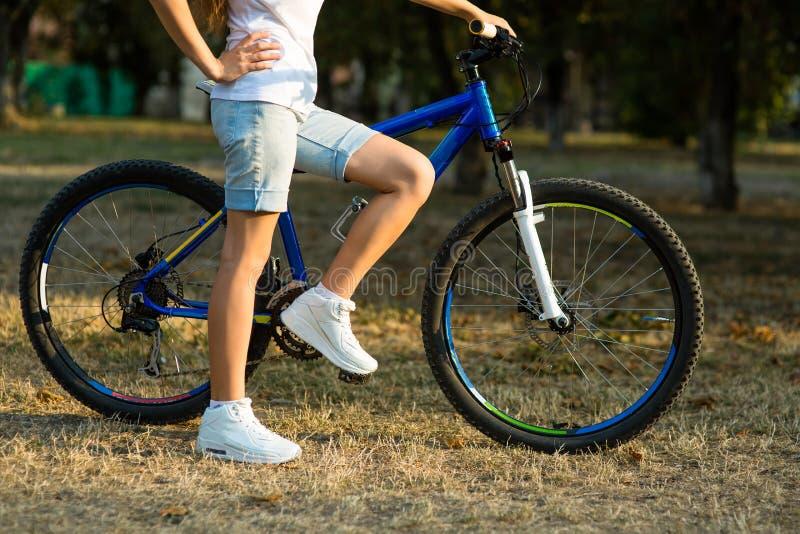 Den tonårs- flickan med cykeln i staden parkerar royaltyfri foto