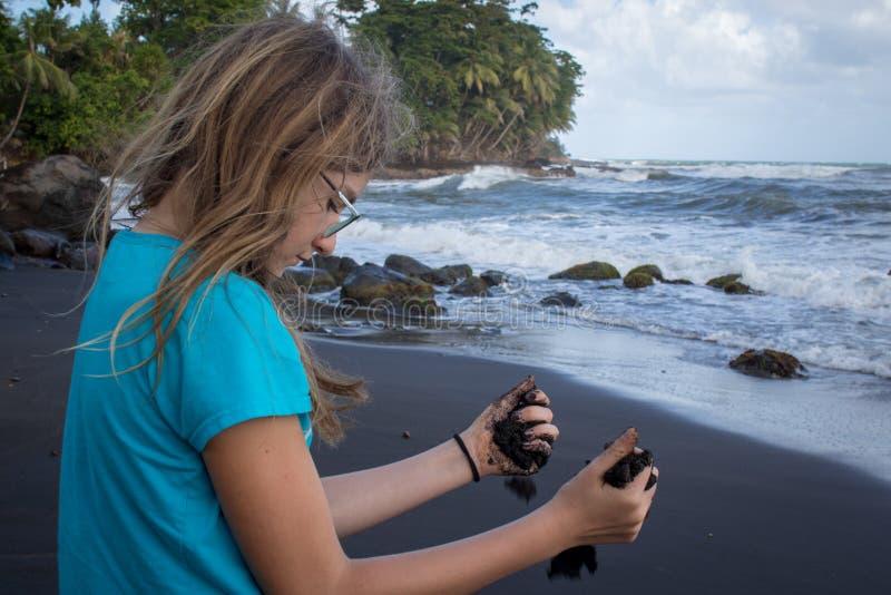 Den tonårs- flickan med gömma i handflatan mycket av vulkanisk svart lavasand arkivfoton