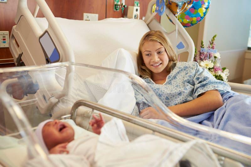 Den tonårs- flickan med nyfött behandla som ett barn sonen i sjukhus royaltyfri bild