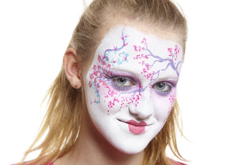Den tonårs- flickan med vänder mot målninggeishaflickan arkivbild