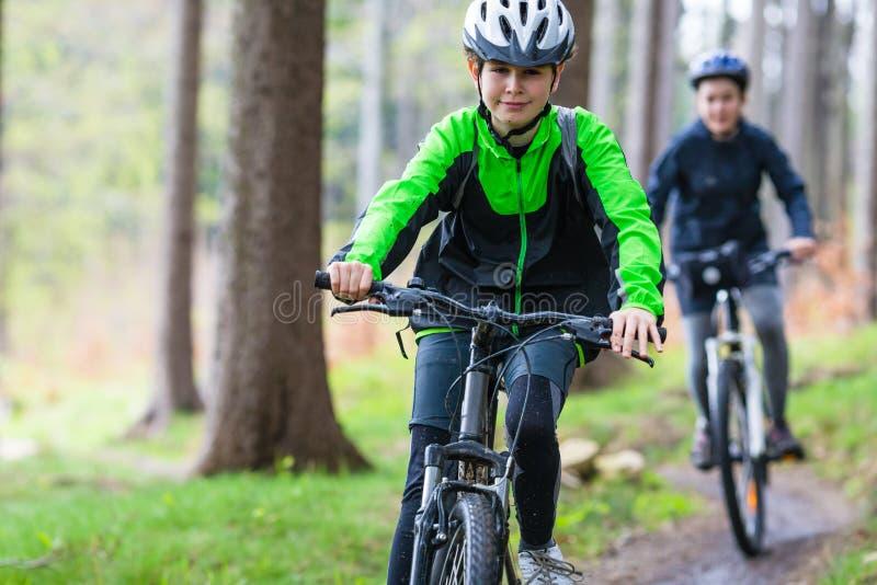 Den tonårs- flickan och pojken som cyklar på skog, skuggar royaltyfri fotografi
