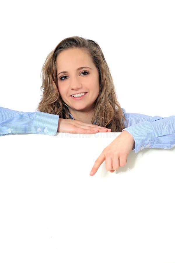 Den tonårs- flickan pekar ner blankt vitt tecken arkivbild