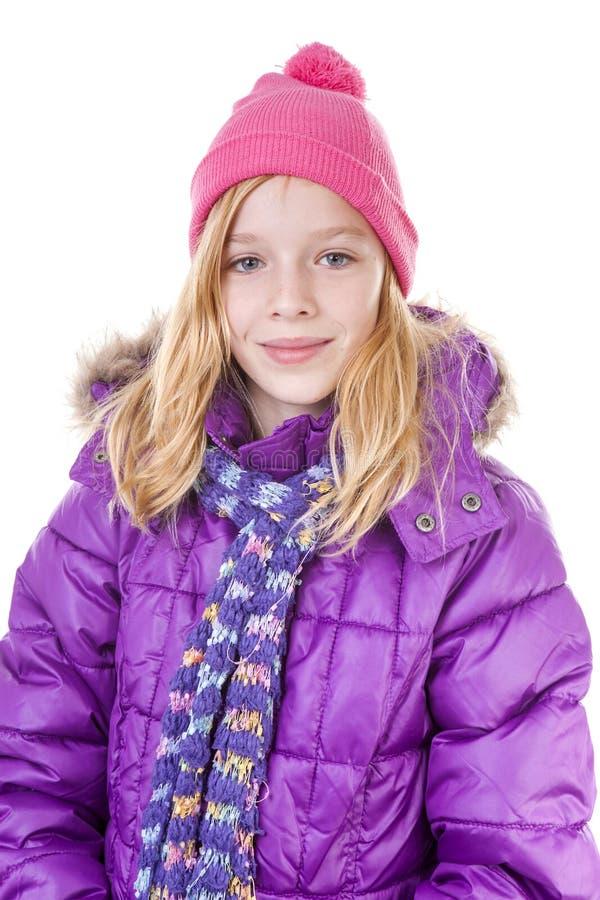 Den tonårs- flickan poserar i vinterdräkt över vit backgroung royaltyfri bild