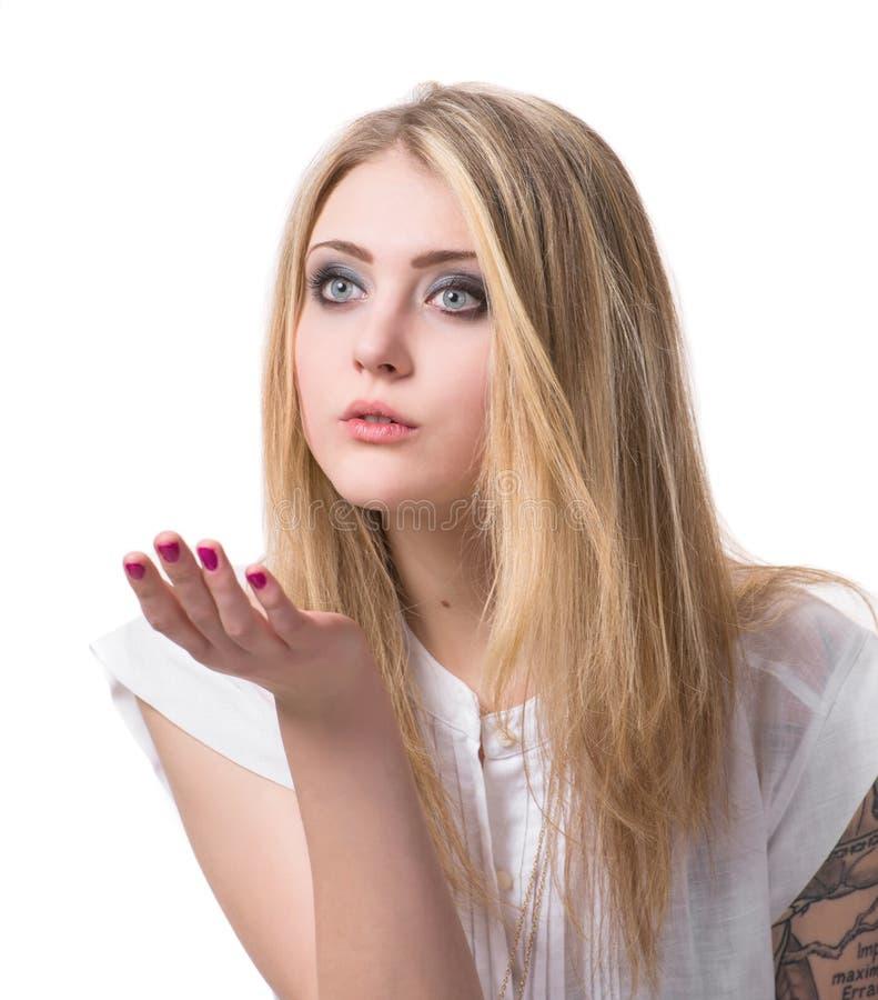 Den tonårs- flickan som blåser på, gömma i handflatan royaltyfri bild