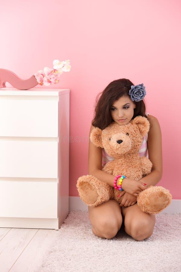 Den tonårs- flickan som kramar nallebjörnen i rosa färger, hyr rum royaltyfria bilder