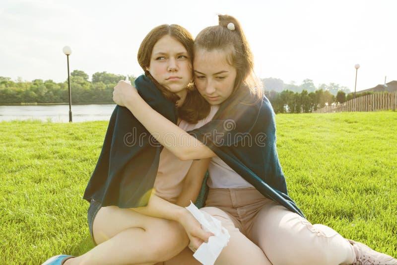 Den tonårs- flickan tröstar hennes skriande, upprivna ledsna flickvän Flickorna sitter på det gröna gräset i parkera fotografering för bildbyråer