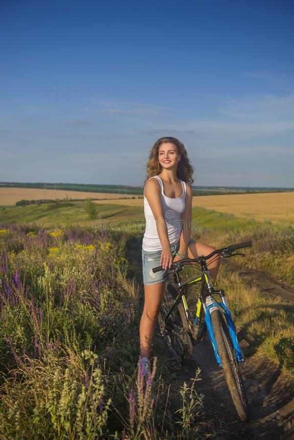 Den tonårs- flickan utanför staden med cykeln fotografering för bildbyråer
