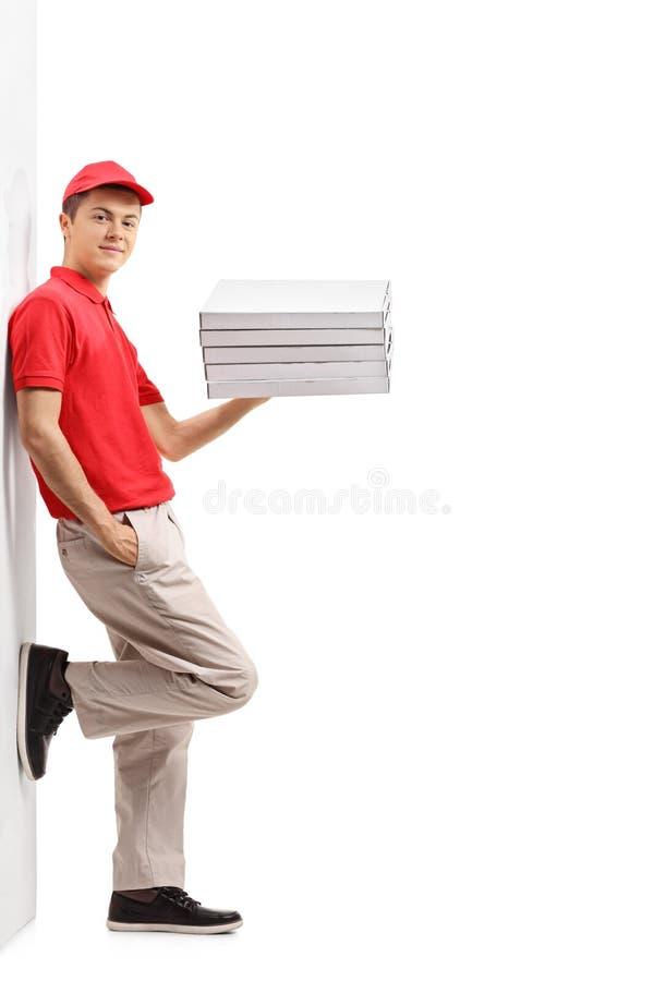 Den tonårs- pizzaleveransgrabben med en bunt av pizza boxas att luta a royaltyfria foton
