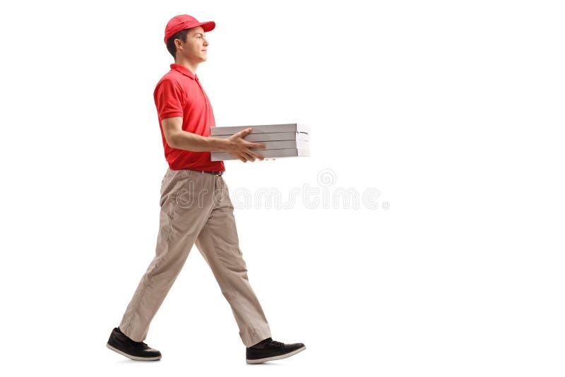 Den tonårs- pizzaleveranspojken med pizza boxas att gå royaltyfri foto
