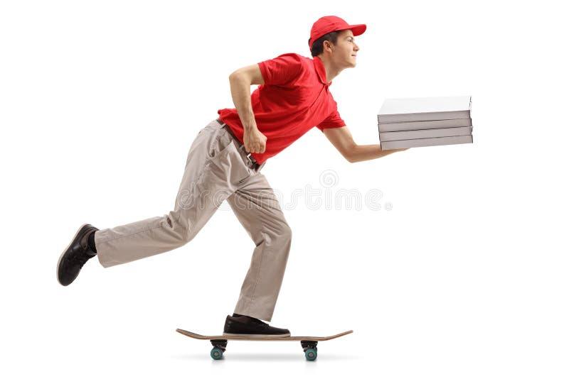 Den tonårs- pizzaleveranspojken med pizza boxas att rida en skateboard royaltyfria foton