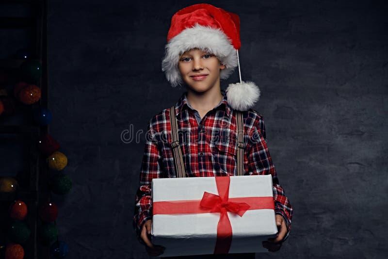 Den tonårs- pojken i hatt för jultomten` s rymmer gåvaasken arkivfoton