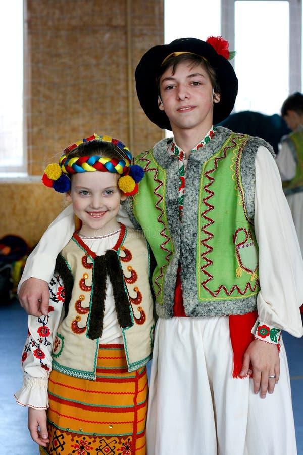 Den tonårs- pojken med flickan är lite i ukrainska nationella dräkter från västra region royaltyfria foton