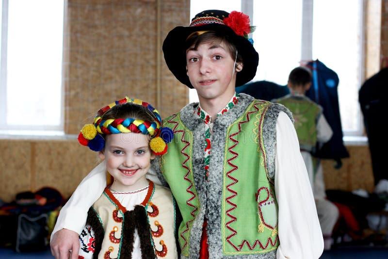 Den tonårs- pojken med flickan är lite i ukrainska nationella dräkter från västra region royaltyfri foto