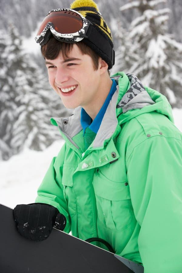 Den tonårs- pojken med snowboarden skidar på ferie royaltyfria bilder