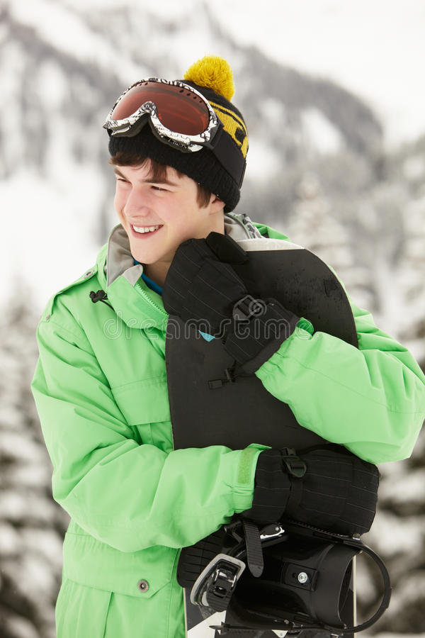Den tonårs- pojken med snowboarden skidar på ferie royaltyfri fotografi