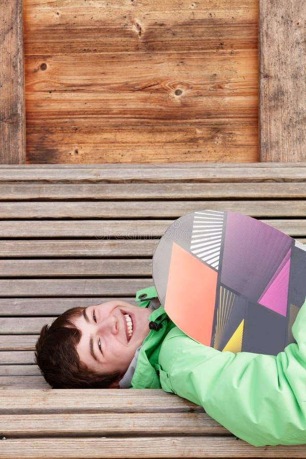 Den tonårs- pojken med snowboarden skidar på ferie arkivfoton