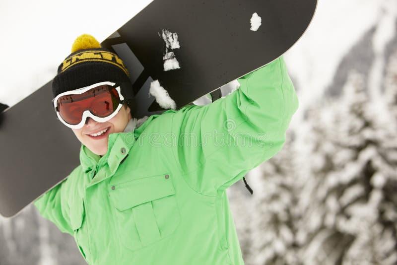 Den tonårs- pojken med snowboarden skidar på ferie fotografering för bildbyråer