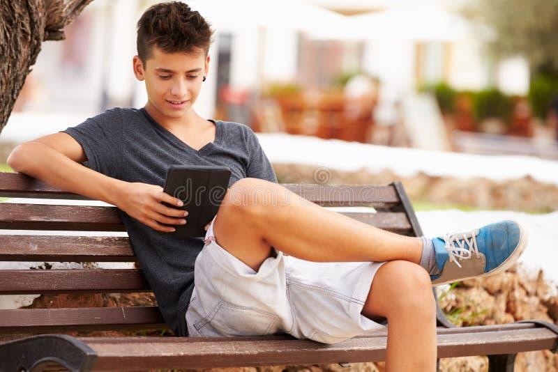Den tonårs- pojken parkerar på bänken genom att använda den Digital minnestavlan arkivfoto