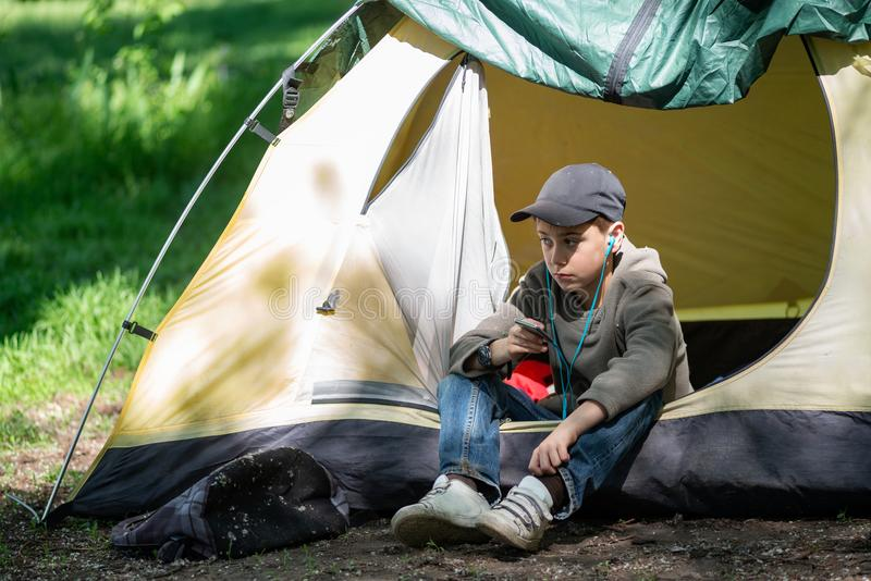 Den tonårs- pojken sitter nära ett tält på en grön äng arkivfoto