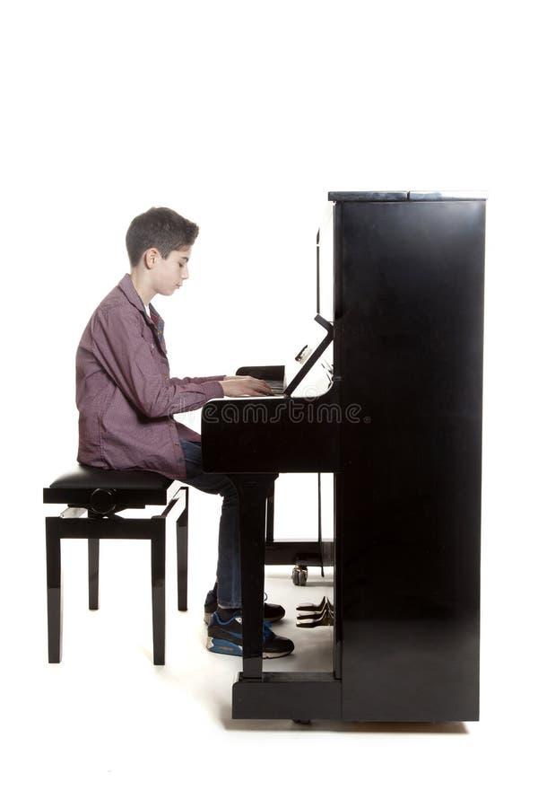 Den tonårs- pojken sitter på det upprätta pianot i studio royaltyfri fotografi