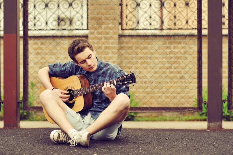 Den tonårs- pojken spelar en akustisk gitarr royaltyfria foton