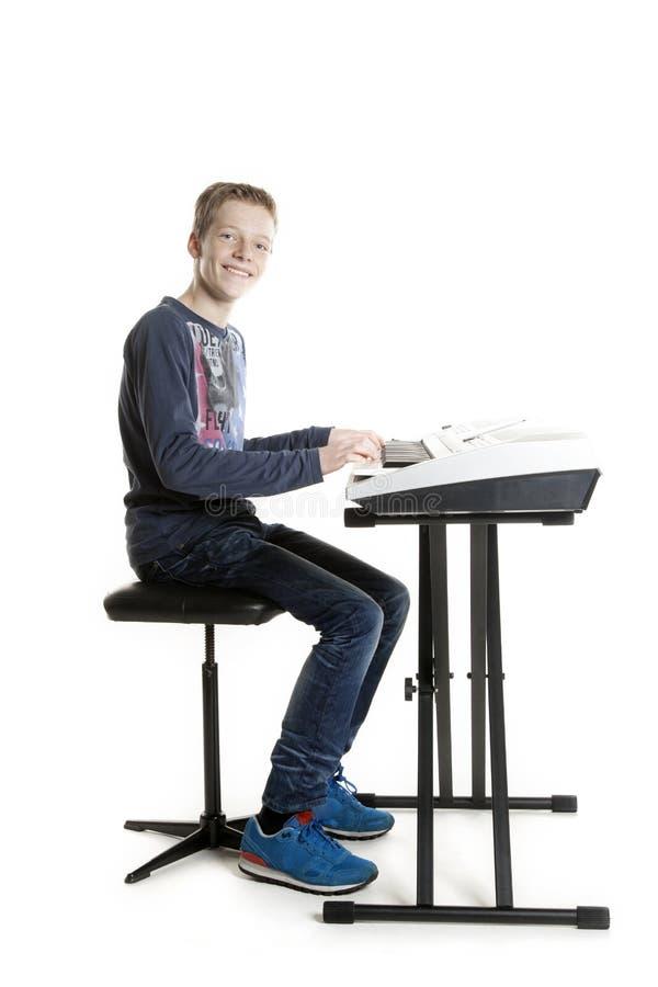 Den tonårs- pojken spelar tangentbordet i studio arkivbild