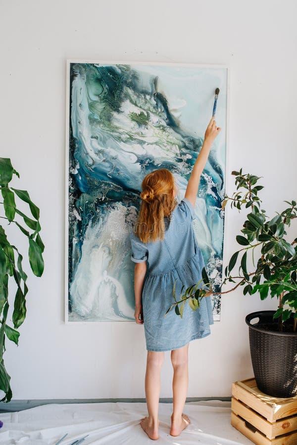 Den tonårs- rödhårig manflickan målar på en kanfas som hänger på väggen royaltyfri foto