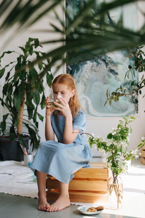 Den tonårs- rödhårig manflickan sitter på en ask som dricker te i ett seminarium royaltyfri foto