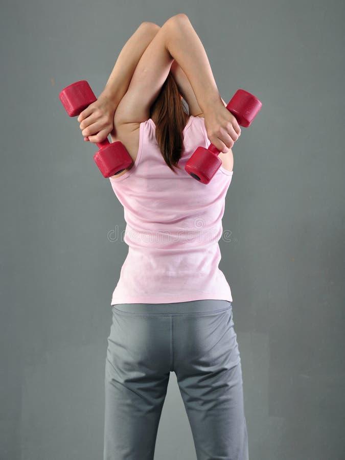 Den tonårs- sportive flickan gör övningar för att framkalla med hantelmuskler på grå bakgrund Sunt livsstilbegrepp för sport Sp royaltyfria bilder