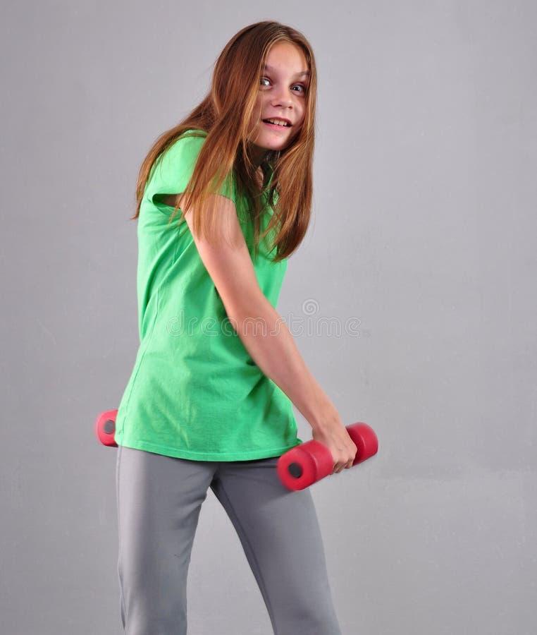 Den tonårs- sportive flickan gör övningar för att framkalla muskler på grå bakgrund Sunt livsstilbegrepp för sport Sportig barndo royaltyfri bild