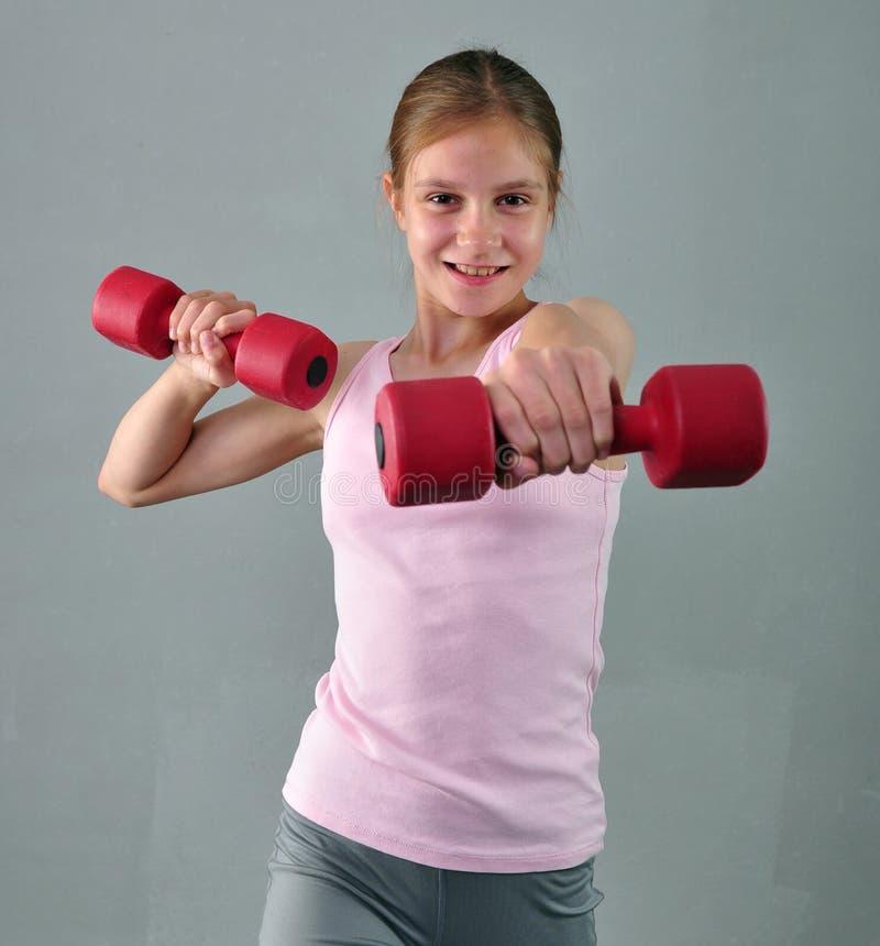 Den tonårs- sportive flickan gör övningar för att framkalla muskler på grå bakgrund Sunt livsstilbegrepp för sport Sportig barndo arkivfoto