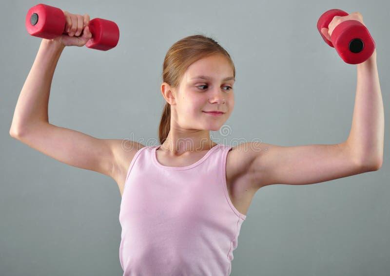 Den tonårs- sportive flickan gör övningar för att framkalla muskler på grå bakgrund Sunt livsstilbegrepp för sport Sportig barndo royaltyfria foton