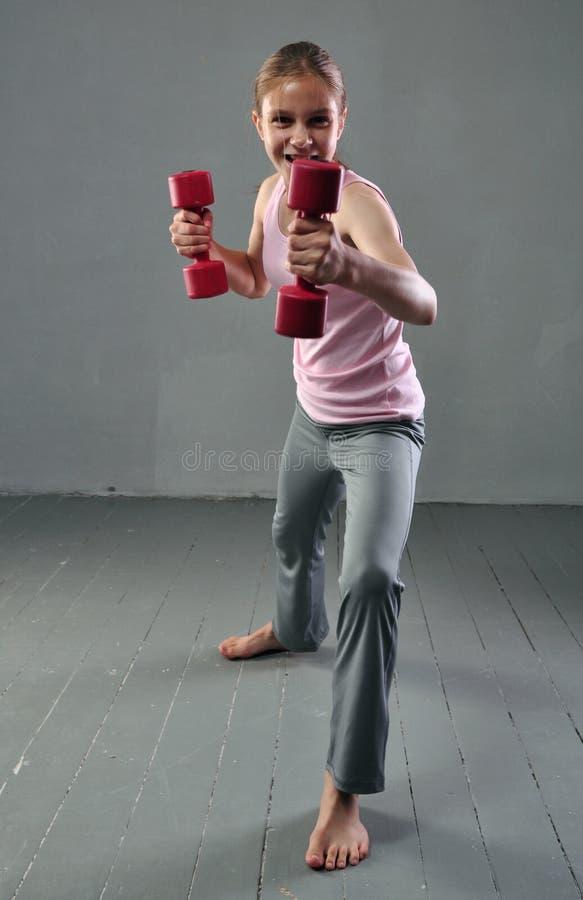 Den tonårs- sportive flickan gör övningar med hantlar för att framkalla med hantelmuskler på grå bakgrund Sund mest lifest för sp arkivfoto