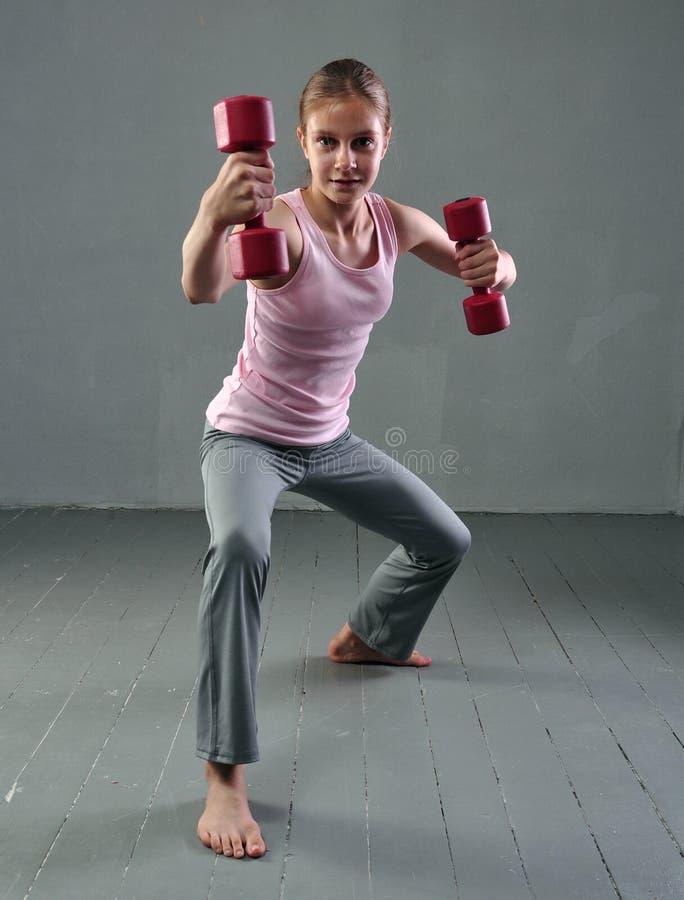 Den tonårs- sportive flickan gör övningar med hantlar för att framkalla muskler på grå bakgrund Sunt livsstilbegrepp för sport Sp arkivfoto