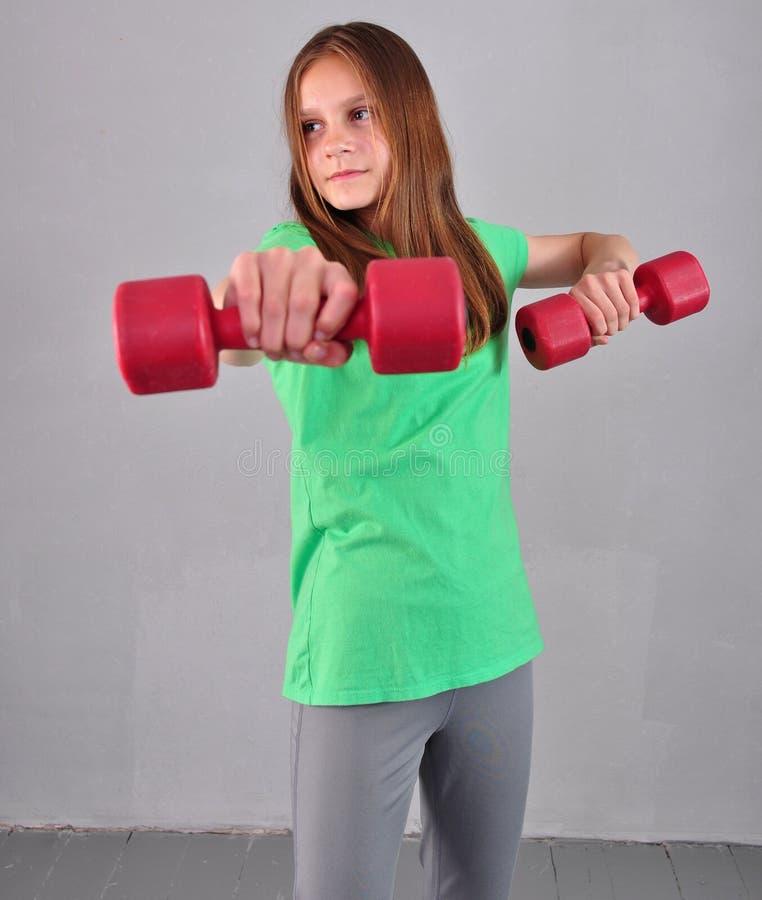 Den tonårs- sportive flickan gör övningar med hantlar för att framkalla muskler på grå bakgrund Sunt livsstilbegrepp för sport Sp arkivfoton