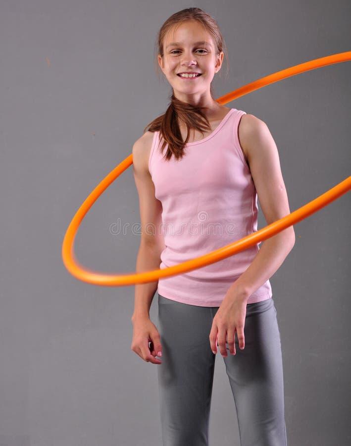 Den tonårs- sportive flickan gör övningar med hulabeslaget för att framkalla muskeln på grå bakgrund Ha gyckel som spelar leken S arkivfoton