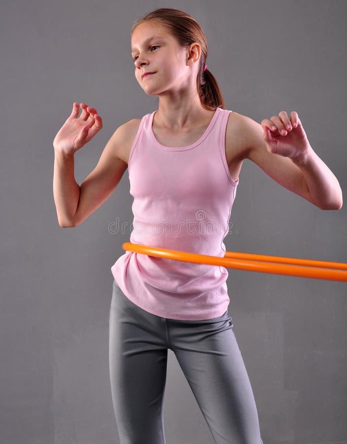 Den tonårs- sportive flickan gör övningar med hulabeslaget för att framkalla muskeln på grå bakgrund Ha gyckel som spelar leken S arkivbild